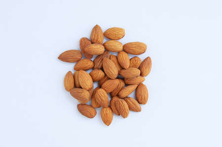 A handful of heap of peeled almonds on a white background.