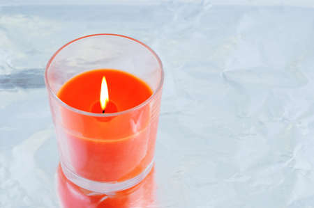 Burning orange aroma candle close-up in a glass on a metallic gray background. View from above.