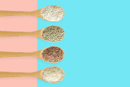 Cereals in a wooden spoon in a row on a pink and turquoise two-tone background.