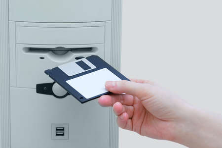 A hand inserts a floppy disk into a personal computer. Retro technology.