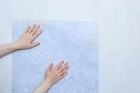 Caucasian woman applies a roll of paper wallpaper to the wall. Hands close up.