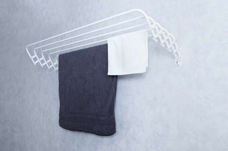 White metal wall-mounted clothes dryer with towels on a gray wall background.
