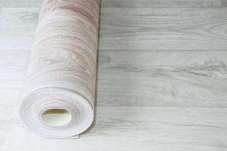 Rolled up roll of beige linoleum with wood texture on white wood floor. Home renovation and improvement.