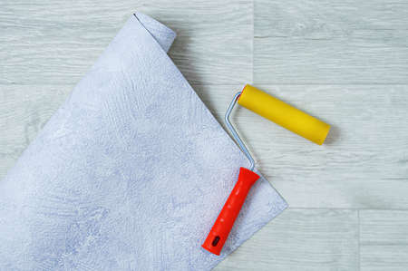Gray textured unrolled wallpaper roll and wallpaper roll.