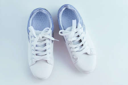 White sneakers with laces with silver inserts on a white background. View from above. 스톡 콘텐츠