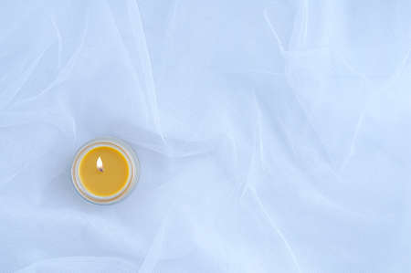 Burning yellow candle in a candlestick on a white organza background. Standard-Bild