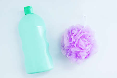 Purple nylon body washcloth and a bottle of shower gel on a white background.