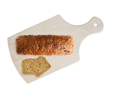 A loaf of wheat bread with seeds and diced slices on a wooden cutting board. White isolate. Standard-Bild