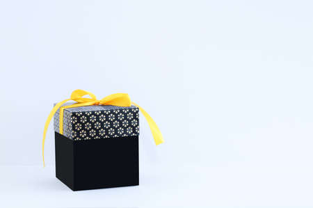 Black gift box with a yellow bow on a white background. Place for your text. Standard-Bild