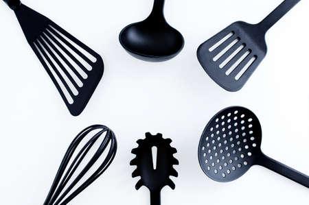 Kitchen utensils for cooking. Black plastic ladle, whisk, ladle on a white background. Standard-Bild