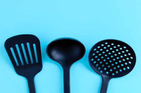 Kitchen utensils for cooking. Black plastic ladle, spatula and ladle on a turquoise background. Standard-Bild