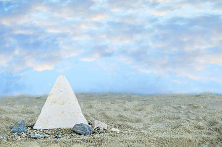 Imitation of a miniature pyramid in the sand against the background of the sky with clouds during the summer day.