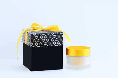 Black gift box with yellow bow and glass jar of face cream on white background. Standard-Bild