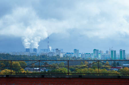 Thermal power plant with smoke from chimneys on the background of the cityscape in the summer afternoon.