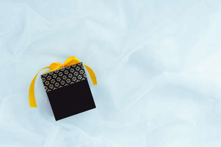 Black gift box with a yellow bow on a white fabric background. Place for your text.
