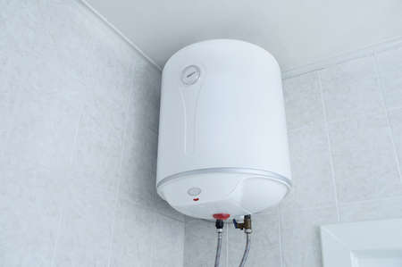 White electric water heater boiler on the wall in the bathroom. Standard-Bild