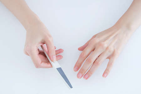 Manicure. Hands of a caucasian woman with a nail file. White background.