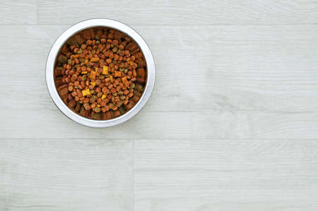 Dry pet food in a metal bowl on a white wooden floor.