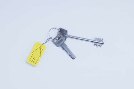 Real estate concept. Keychain with keys with black lines sketch of a house.