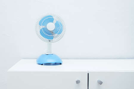 Small desktop electric fan of air in the room on the dresser.