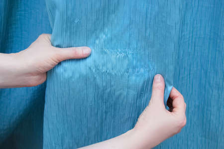 Damaged blue tissue. Puffs on the curtains. Cloth in hand.