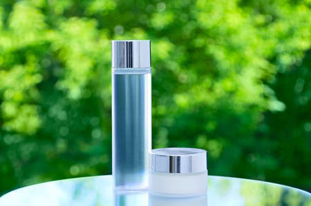 Face cream in a glass jar and lotion in a transparent bottle on a mirrored tabletop against a background of green foliage.