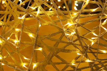 Yellow background of intertwined wooden branches with lights. Soft focus.