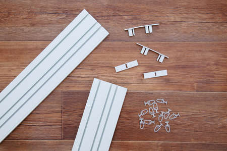 White plastic ceiling curtain rod with assembly hardware and hooks. On a brown wooden background.
