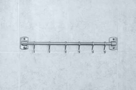 Metal hanger in the bathroom against the background of white tiles.