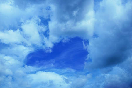 Blue sky with clouds in the shape of a heart during the day outdoors.