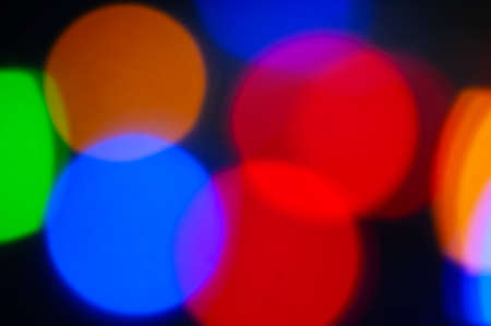 Multicolored bokeh on a black background. Blurred focus.