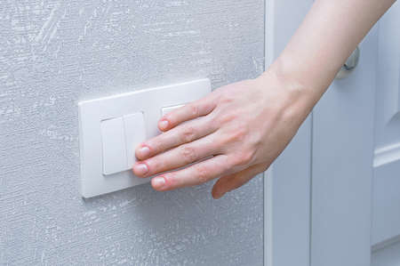 Close-up hand of caucasian woman turns on the wall light switch in the room.