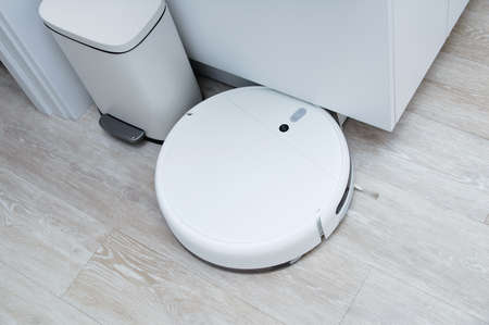 White robot vacuum cleaner collided with an obstacle on the kitchen floor.