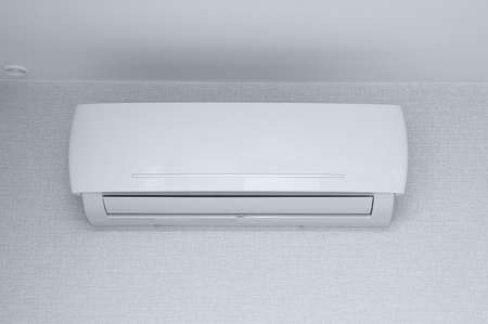 Air conditioner on the wall in the room against the background of white wallpaper.