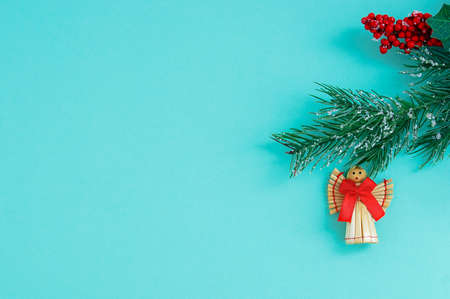 Christmas straw angel with a red bow on a branch of a Christmas tree. Turquoise background.