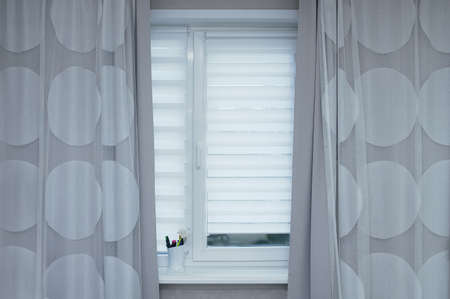 White blinds and gray curtains on the window in the room. Standard-Bild