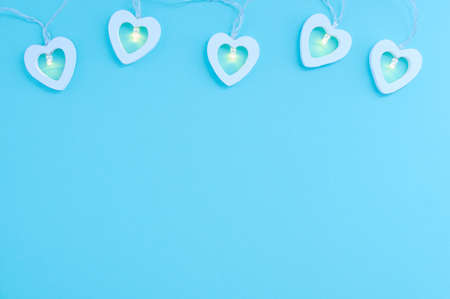 Electric white garland with glowing lights in the form of hearts on a blue background. Place for your text.
