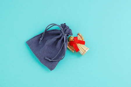 Christmas straw angel with red bow and gray canvas pouch. Turquoise background. Standard-Bild