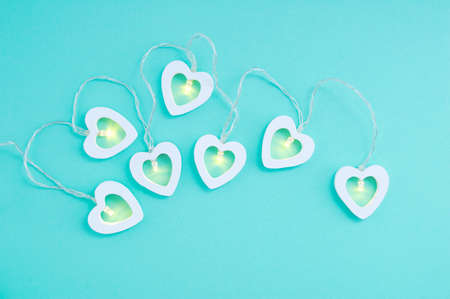Electric white garland with glowing lights in the form of hearts on a turquoise background.