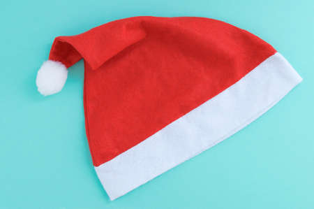 Red santa hat on a turquoise background close-up.