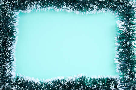Christmas green tinsel frame. Turquoise background. Place for your text. Standard-Bild