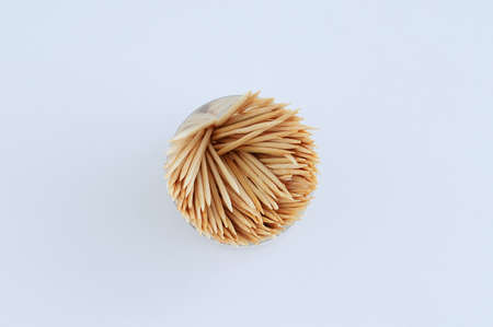 Wooden toothpicks in a round package on a white background close-up.