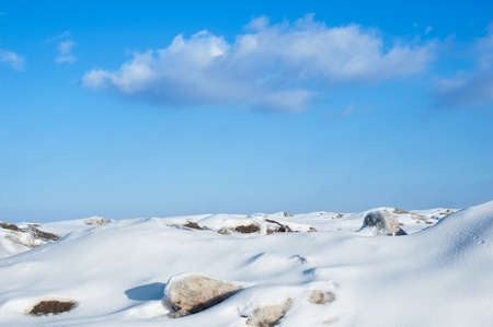 Snowy winter landscape in the mountains with blue sky with clouds. During the afternoon in sunny weather. Standard-Bild