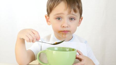 The child with pleasure eat soup from dishes with a spoon, close-up