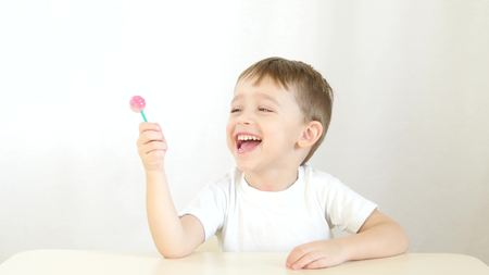 Happy child smiling and eating lollipops on a stick, sitting at a table on a white background - 3