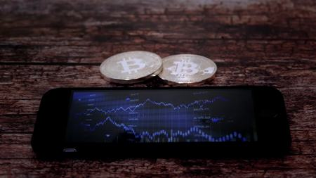 Two coins bitkoyn, lying next to the smartphone, on the screen which displays a chart of quotations, crypto currency. 스톡 콘텐츠