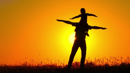 A small child spinning on his fathers shoulders. Happy family playing at sunset. Silhouette. 스톡 콘텐츠