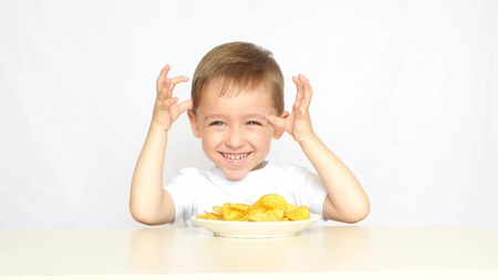 The child closes his eyes with his hands in anticipation of delicious potato chips. The child is served a plate with potato chips. The boy eats crisps.