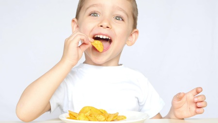 A child with pleasure eating potato chips sitting at a table on a white background. The boy is eating chips and smiling. Foto de archivo