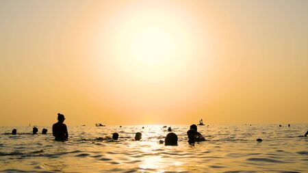 A group of people swimming in the sea on the beach at sunset.